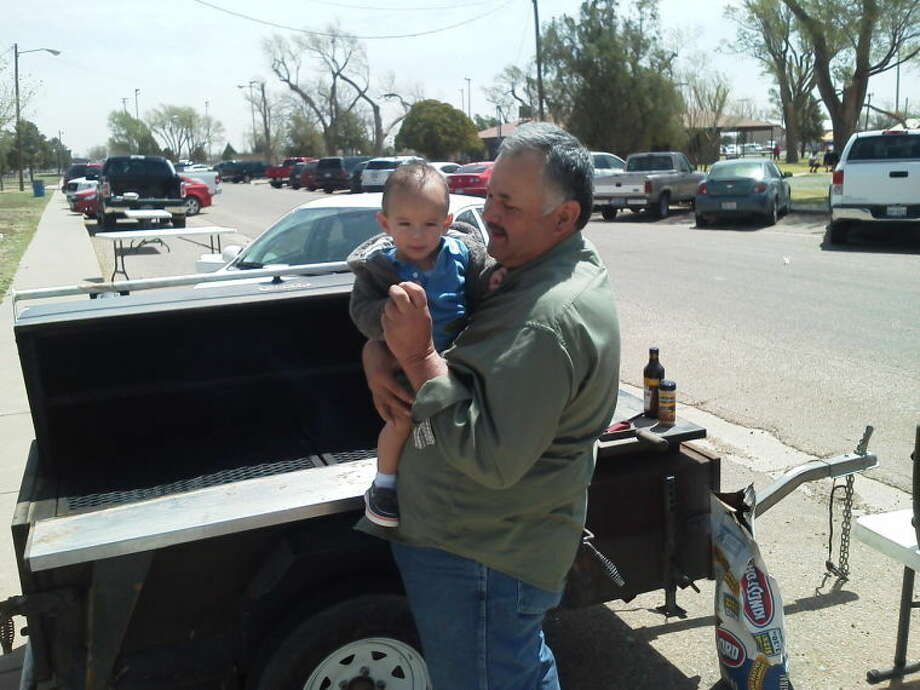 Cook Ruben Renteria takes a break from barbecuing to hold his grandson and future griller Brayden. Photo: Courtesy Photo