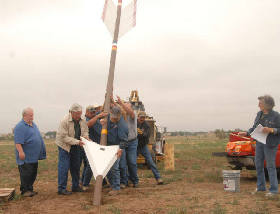 In a scene reminiscent of the Iwo Jima flag raising, city parks employees and others place Plainview's Quanah Parker Trail Arrow at the Plainview Point site on Thursday. Helping muscle the 22-foot shaft into place are Randy Vance (left) of Texas Tech's Southwest Collections, arrow creator Charles Smith of New Home, Joe Salias, Fred Pena, Jerry Haney, Tim Salazar, Dr. Sam Van Hoose of Wayland, and Ricky Summer. Local project facilitator Corky Terrell is at right. Photo: Doug McDonough/Plainview Herald