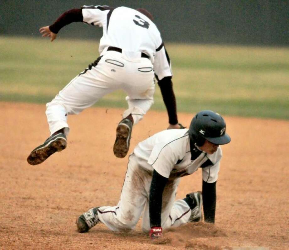 As the Midland Lee first baseman jumps over him to chase down an errant pick-off, Plainview's Trey Hernandez prepares to get up to race to second during the Bulldogs' home opener Monday. Photo: Kevin Lewis/Plainview Herald