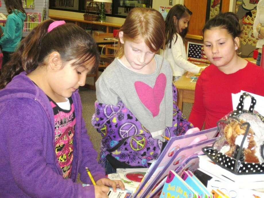 Jan Seago/Plainview ISDLa Mesa Elementary students Makai Varela (left), Lexi Robertson, Kaitlyn Burdge and Julissa Gonzales (background) visit the Scholastic Book Fair to preview available books. Scholastic Book Fairs will be available in the La Mesa, College Hill and Lakeside school libraries during Texas Public School Week to allow parents to attend with their children.