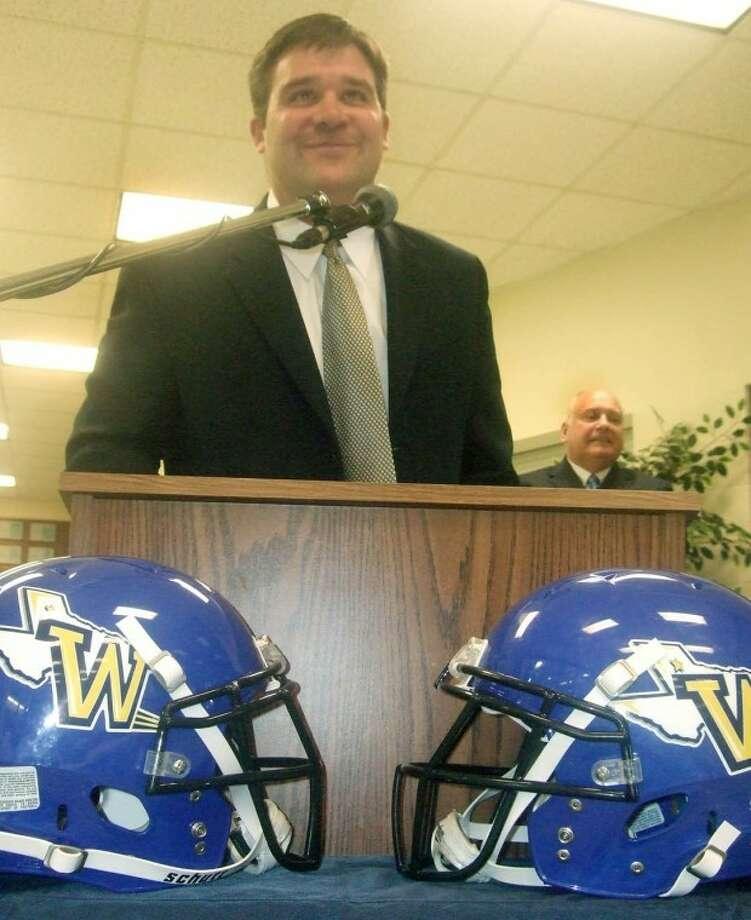 Jeff Lynn speaks at a press conference after being introduced by Wayland Director of Athletics Dr. Greg Feris (background) on Wednesday afternoon in the lobby of Hutcherson Center. About 75 people showed up to welcome Lynn, the head coach for the last six years at New Mexico Military Institute in Roswell. The Pioneers will play their first official football season in more than 70 years in 2012