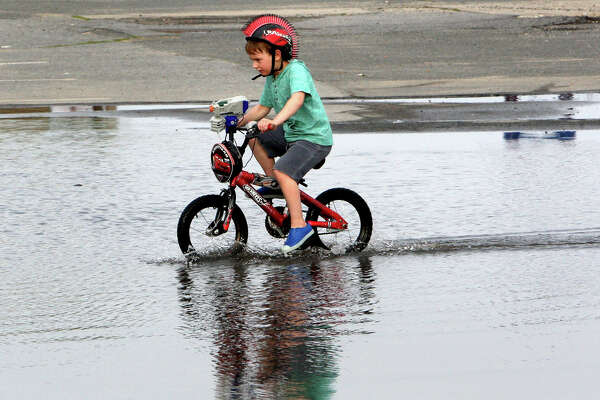 NEWBURYPORT, MA - JUNE 23: Giant puddle from heavy rain on Plum Island earlier in the day proved irresistible for five-year-old Jake Lively as he rode his bicycle on the Newburyport, Mass, end of the island June 23, 2015. (Photo by John Blanding/The Boston Globe via Getty Images)