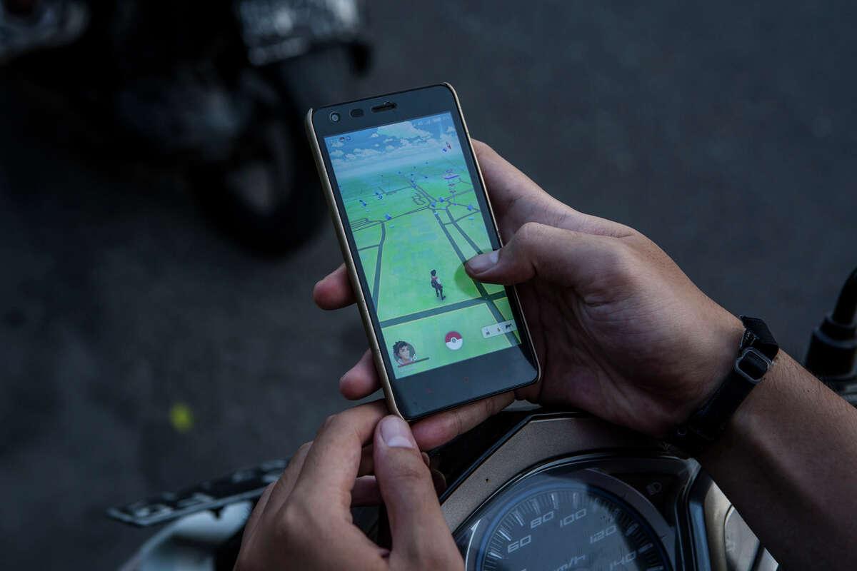 YOGYAKARTA, INDONESIA - JULY 24: A motorcyclist, plays Pokemon Go game on his smartphone on July 24, 2016 in Yogyakarta, Indonesia.