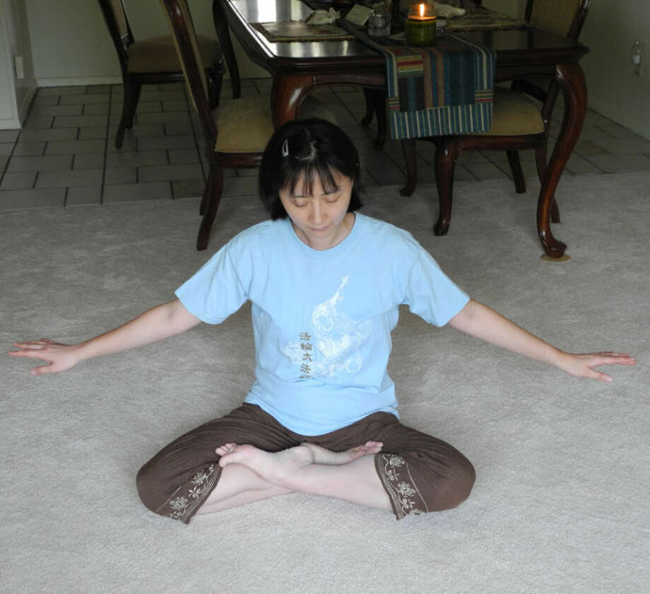 Yan Wang, 39, demonstrates a Falun Gong pose. Falun Gong, a series of yoga-like exercises, was banned in China. Wang was among its practitioners who were persecuted.