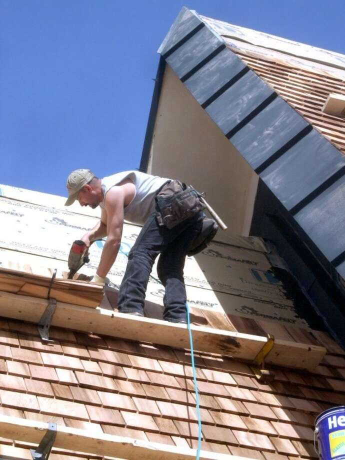 Kevin Lewis/Plainview HeraldBenny Diaz of Dickerson Roofing very carefully applies new material onto the steep roof of the chapel at Lemons Funeral Home on Thursday.