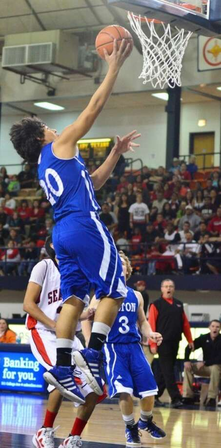 Olton's Chris Favela (20) drives for a lay-up in Saturday's regional championship game against Seagraves. The Mustangs won to advance to the state tournament for the first time ever. Photo: Albert Gomez