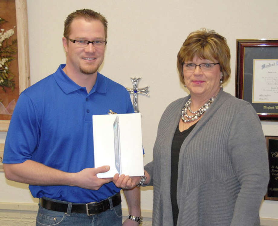 Courtesy PhotoJohn Zais, a student at Wayland Baptist University's Lubbock campus, is presented an iPad 2 for his winning essay by WBU Director of Web Services Charlotte Schumacher.