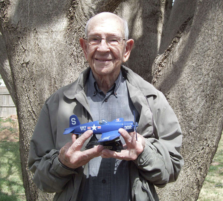 WWII Navy vet Vaughn Hunter, 90, shows off an F4U Corsair model like the one he flew in combat. He's standing by a tree he planted in 1952. Photo: Shanna Sissom/Plainview Herald