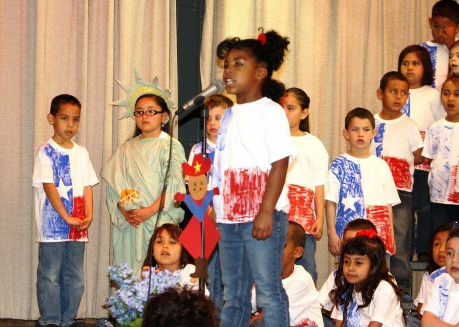 Jan Seago/Plainview ISDSurrounded by fellow first-grade students, Antonia Bozarth-Leos steps up to the microphone during the annual Wee Sing America program last week to tell an audience of parents and community members that Texas was admitted to the United States in 1845 as the 28th state. College Hill first-grade teachers responsible for organizing the program of American and Texas history and songs were Wistie Rollins, Joyce McCormick, Ida Rascon and D'Anna Kellum.