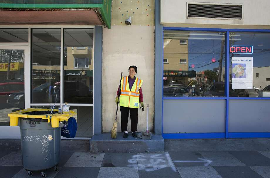 Suu Ngo cleans a sidewalk along Irving Street, top, in the Inner Sunset. Ngo, shown in her apartment with her dog, above, headed to City Hall for a job after 27 years of restaurant work so she could take care of her grand children. Photo: Erin Brethauer, The Chronicle