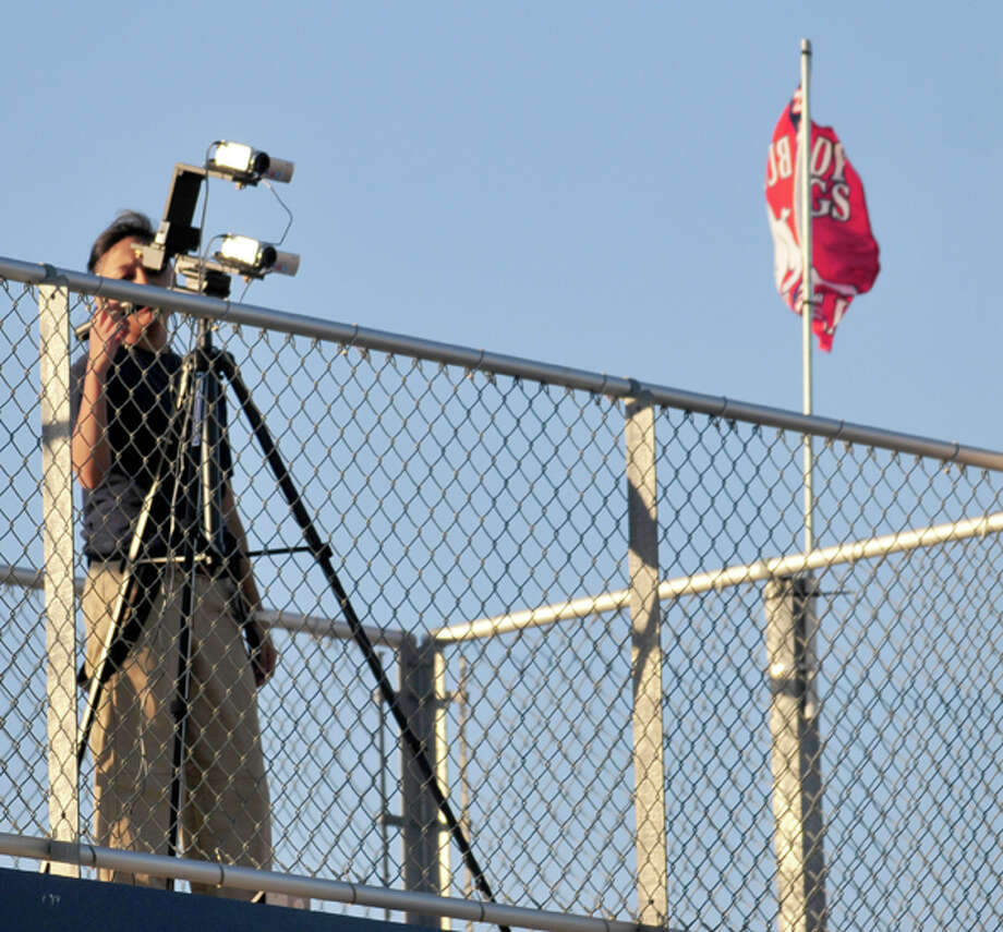 Standing atop the pressbox at Lady Bulldog Park, Plainview High School junior Mayra Chavarria films the action during Tuesday's game between Plainview and Hereford.