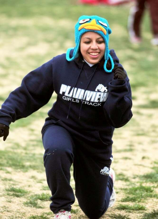 Plainview High School sophomore Stacey De La Garza sports a colorful cartoon character cap as she attempts to warm up during last Friday's Reagor-Dykes Bulldog Relays at Greg Sherwood Memorial Bulldog Stadium. Warming up has been a lot easier the last couple of days when temperatures, after being in the 30s and 40s last weekend, have risen into the 80s the last two days. The weekend forecast also looks nice, with a 30 percent chance of thunderstorms Friday. Photo: Kevin Lewis/Plainview Herald