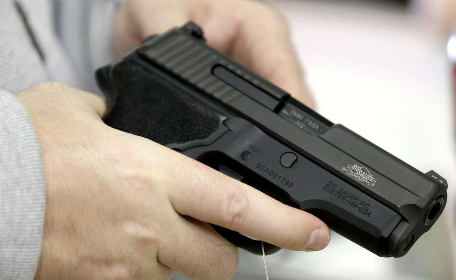 A man holds a handgun while shopping at a gun store in Spring, Texas.