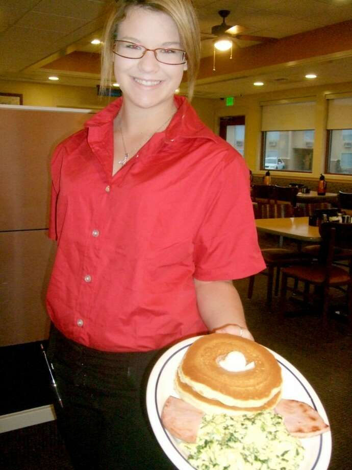 As part of a St. Patrick's Day promotion on Saturday, IHOP offered a green eggs and ham special. The eggs weren't actually green, but blended with spinach. Here, Ashley Langston serves up a plate, complete with pancakes.