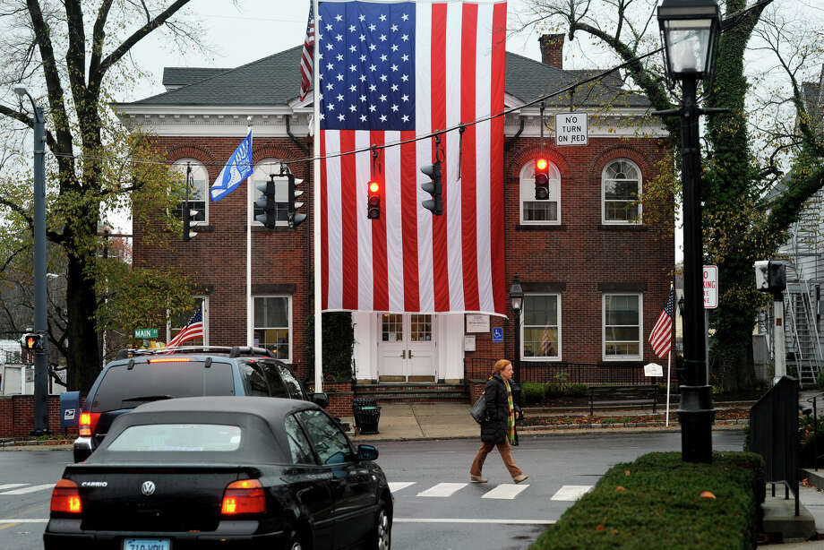 A large American flag hangs in front of Ridgefield Town Hall, at the intersection of Main St. and Bailey Ave. in Ridgefield, Conn. Nov. 12, 2015. Photo: Ned Gerard / Hearst Connecticut Media / Connecticut Post