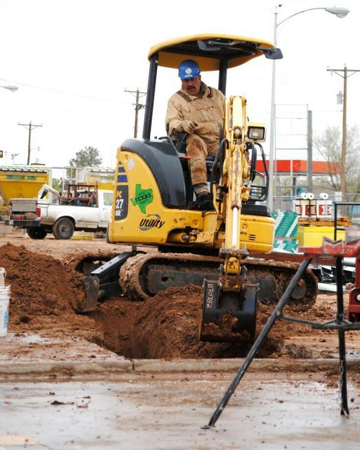 Doug McDonough/Plainview HeraldProtected from rain by a partial roof over his backhoe, Mike Rivas of Amarillo fills a water main trench Monday at the new addition to Plainview High School. Employed by Texas Plumbing, Rivas said his part of the project was not hampered by Monday rainfall. Plainview received 0.37 inch of moisture before dawn Monday with an additional 0.02 inch recorded throughout the day. That brings Plainview's 2012 rainfall to date to 1.18 inches, compared to 1.37 inches for the same period in 2011.
