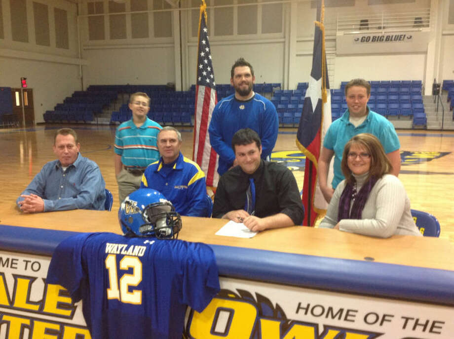 Hale Center Owl lineman, Garrett Tiner, is joined by family as he signs a commitment to play football with the Wayland Baptist University Pioneers. Photo: Homer Marquez/Plainview Herald