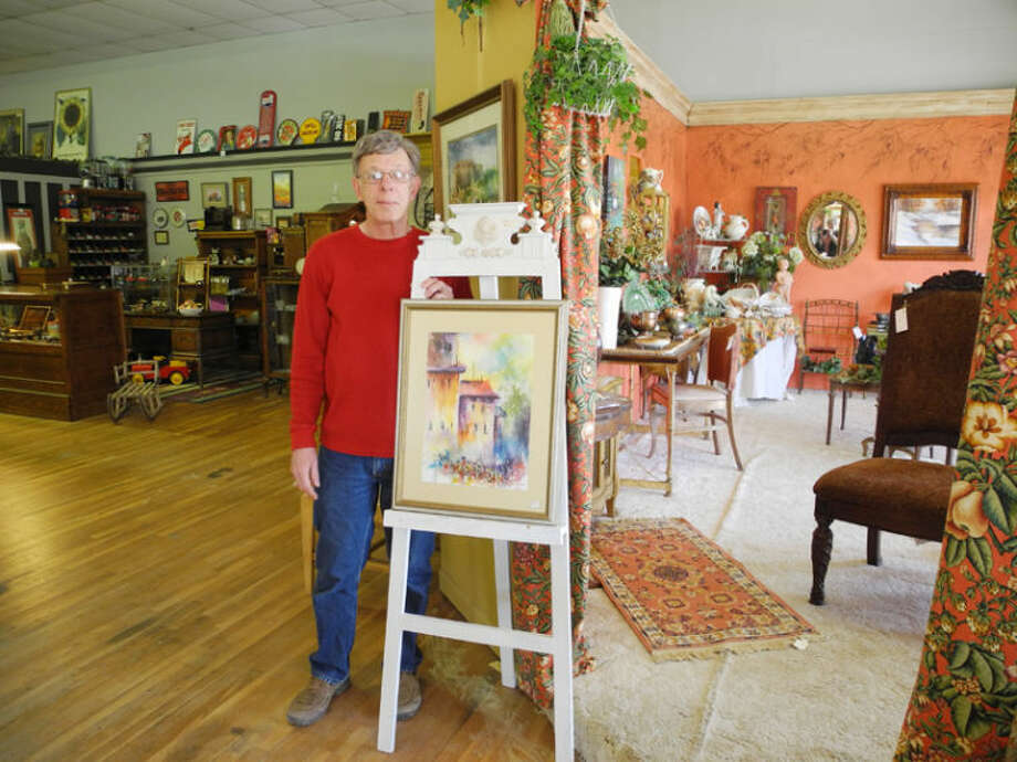 Ricky Davis, owner of Uniques & Antiques, stands next to one of his pastels. In the background are rooms he decorated to display his antiques. Many of his own paintings hang on the walls. Photo: Gail M. Williams | Plainview Herald