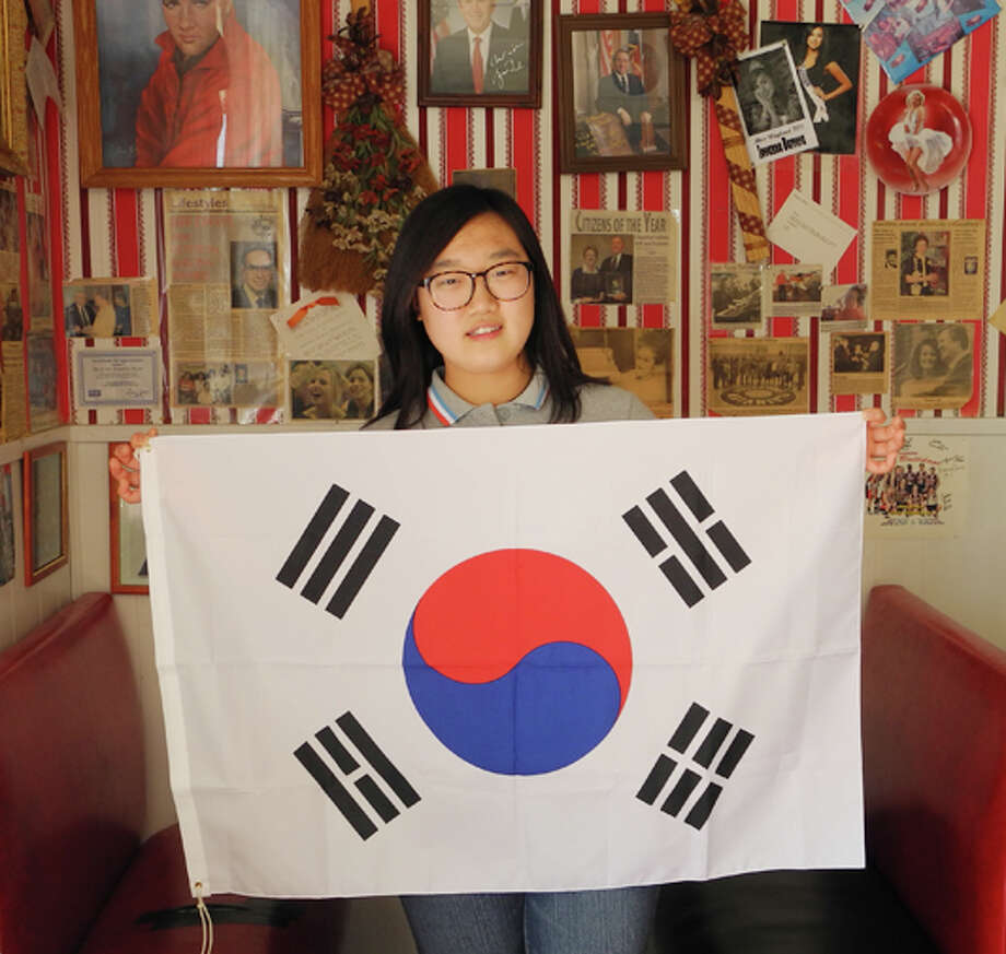 Surrounded by American cultural icons at the Roaring 50s café in Plainview, South Korean exchange student Haeun Kim holds up her country's flag. The yingyang symbol stands for perfect balance, and each of the four trigrams in the corners have a different meaning. Photo: Gail M. Williams | Plainview Herald