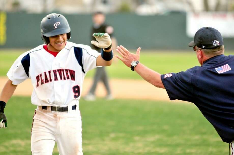 Plainview assistant baseball coach Eric Wilson congratulates Jordan Vera (9) after a base hit during a recent game at Bulldog Park. The Dogs host Hereford at 5 p.m. today while the Lady Bulldog softball team plays in Dumas at 6:30. Wayland's Pioneers host Mid-America Christian in a doubleheader at 4 p.m. today followed by a single game at 1 p.m. Saturday.