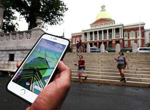 In this Monday, July 18, 2016, photo, a Pokemon Go player shows his mobile phone while walking through the Boston Common, outside the Massachusetts Statehouse in Boston. (AP Photo/Charles Krupa)