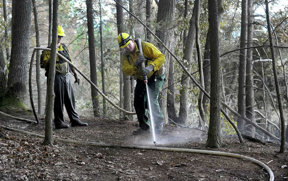 Rich Opalnenik, left, and Jeff Dery, with the Connecticut Department of Environmental Protection, are part of a crew still working Monday afternoon, July 25, 2016,  to put out a fire at Lovers Leap State Park. The Park in New Milford reopened Monday after a massive brush fire that burned through the weekend was put out Sunday evening, according to the state's Department of Energy and Environmental Protection. Photo: Carol Kaliff / The News-Times
