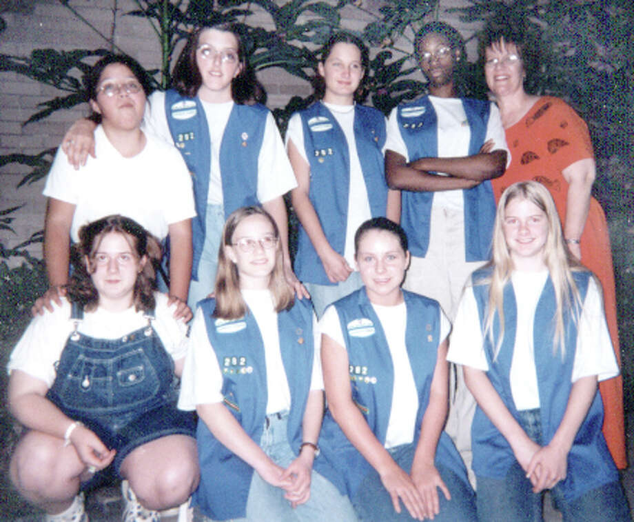 Hayley Cox (bottom row, second from left) is pictured with her Girl Scout troop, which was overseen by her mother, Nancy Cox (back row, far right.)