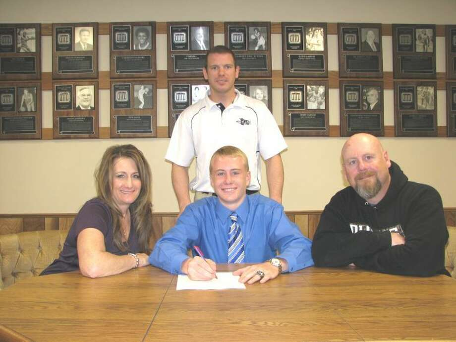 New Mexico state wrestling champion Wyatt Hardy signs a letter of intent to join the Wayland Baptist wrestling team this fall as his parents, Darin and Lauren Hardy, and WBU assistant coach Aaron Meister look on. Photo:  Summer Morgan/Wayland Baptist University
