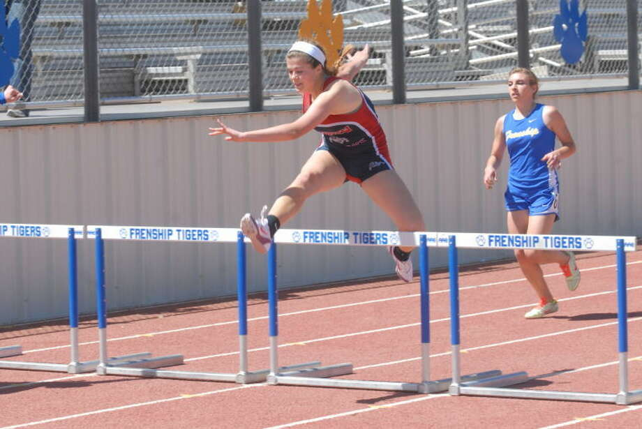 Brooke Walker (top) clears the hurdle during Thursday's final of the 4-4A district track championship. Photo: Homer Marquez