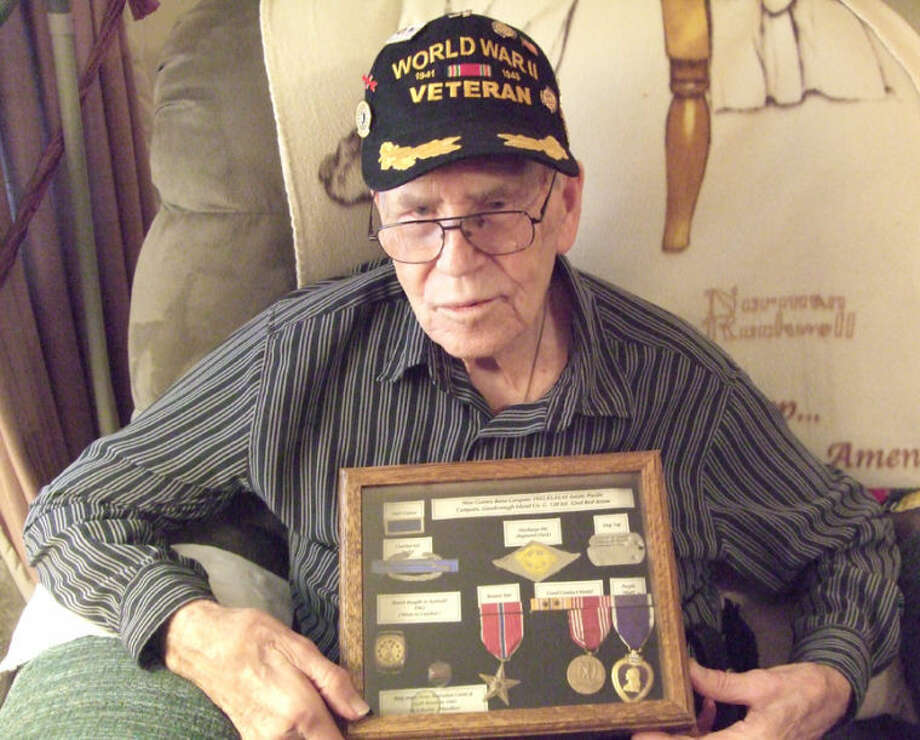 The Rev. R.L. Owens sits with his Purple Heart, Bronze Star and other World War II-era Army medals inside his Zephyr Street home in Plainview. Photo: Shanna Sissom/Plainview Herald