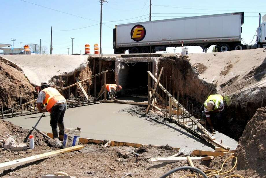 Not all the work on the Fifth Street/Olton Road rebuilding project is taking place at ground level. Texas Department of Transportation employees Richardo Rodriguez (left), David Gutierrez and Gabriel Davora of Wichita Falls were working fresh concrete Thursday in the Running Water Draw diversion channel in the 500 block of West Fifth. Concrete skirting on the culvert is being replaced as part of the road rehabilitation.