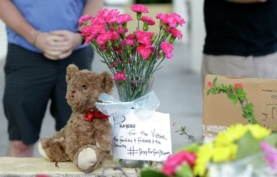 Flowers and stuffed animals are left for the victims of a deadly shooting outside the Club Blu nightclub in Fort Myers, Fla., on Monday. Police said the gunfire, which erupted at a swimsuit-themed party for teens, was not an act of terrorism. Photo: Lynne Sladky, STF / AP