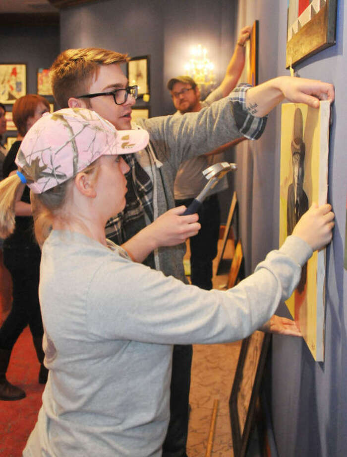 "Katy Powell and Ian Pyeatt hang an art piece at the Abraham Art Gallery for the student art show ""Reflections."" Photo: Courtesy Photo 