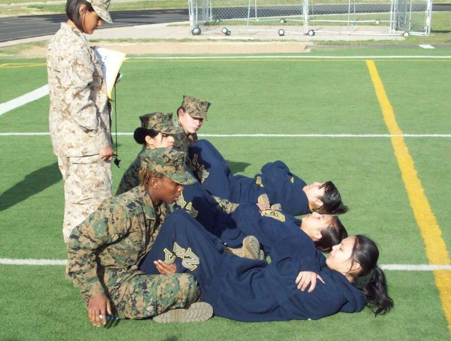 Performing sit ups during the 26th Annual Caprock High School Marine JROTC competition are PHS Navy JROTC students Angel Ostergren (front), Monique Gonzales and Brenda Magana.