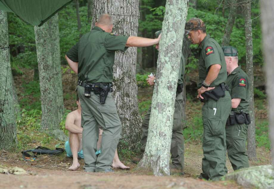 A young man is questioned by New York State Rangers during Log Bay Day, the annual party on the water on the east side of Lake George at Log Bay on Monday July 25, 2016 in Fort Ann, N.Y. A ranger was concerned he had passed out surrounded by cups and cans on his float. The young man might have been underaged. (Lori Van Buren / Times Union) Photo: Lori Van Buren / 20037423A
