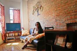 Ashley Warmington, CEO of Cozy Oasis, a short-term rental concierge company, sits in the living room of a property that she manages listings for in New York, Thursday, July 21, 2016. Warmington is partnering her companyÂ?'s services with the anti-racism lodging website Noirbnb. Noirbnb aims to be sensitive to the needs of multicultural travelers who have complained about being rejected for bookings on Airbnb.com because of their race. (AP Photo/Bebeto Matthews)