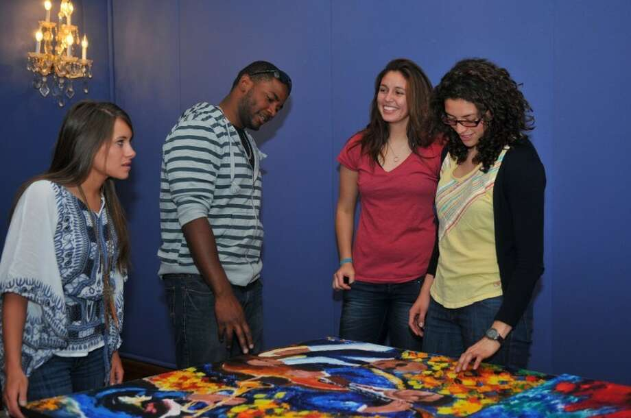 Jonathan Petty/Wayland Baptist UniversitySenior art students Ashley Woodall (left), Gilberto Reyes, Tatiana Gonzalez and Kate Trejos prepare to hang the artwork for their senior art practicum in the Malouf Abraham Art Gallery located in the basement of Wayland's Mabee Learning Resources Center. A reception for the artists will be held from 6-7:30 p.m. Friday.