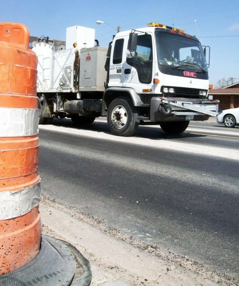A machine paints stripes along Fifth Street where crews have finished the initial reconstruction of the road. When the entire project is complete east to Milwee Street, projected to be late this summer, the Texas Department of Transportation will add a final two-inch top course to even out the new roadway with parking lot entrances.