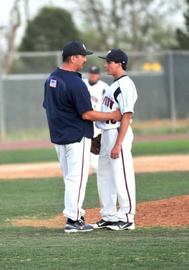 Friday's game against Randall proved challenging for Plainview pitchers, including Brent Silvas. Here, pitching coach Jerry Estrada tries to settle him down. The Bulldogs lost 20-1.