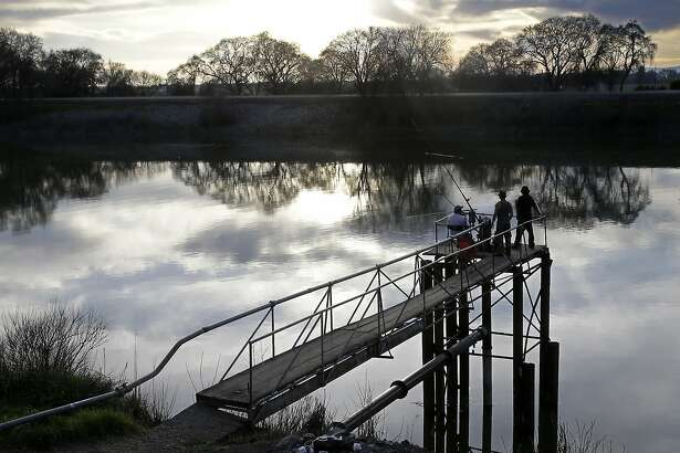 FILE - In this Tuesday, Feb. 23, 2016, file photo, people try to catch fish along the Sacramento River in the Sacramento-San Joaquin Delta, near Courtland, Calif. The California Supreme Court is set to issue a ruling Thursday, July 21, 2016, that could add millions of dollars to the governor's $15.7 billion plan to build two giant water tunnels in the Sacramento-San Joaquin Delta. (AP Photo/Rich Pedroncelli, File)