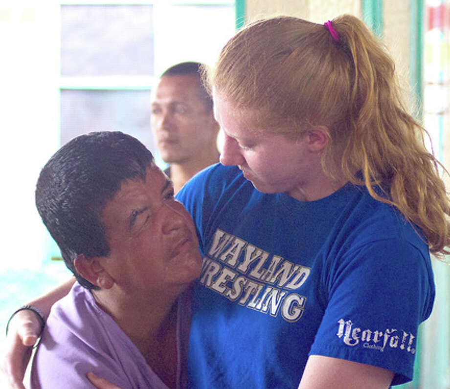 Wayland student Erin Miller hugs a patient at a psychiatric hospital during the university's medical mission trip to Honduras this spring.