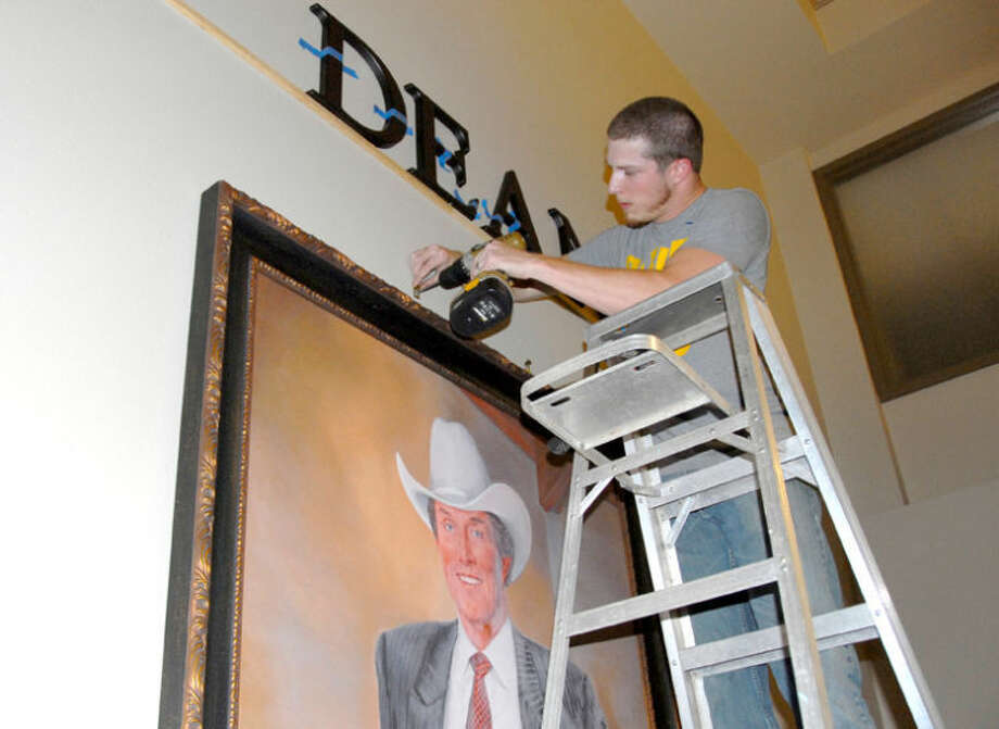 Jonathan Petty/Wayland Baptist UniversityDavid O'Brien of O'Brien's Frames and Things hangs a large portrait of Jimmy Dean which will be on display in Jimmy Dean Hall, Wayland's new men's residential dormitory. The portrait and other photos will be on display today during an open house and dedication from 2-3:30 p.m.
