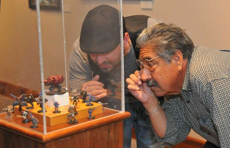 "Richard Porter/Wayland Baptist UniversityWayland art student Angel Azua (left) looks with his father, Salvador, at a collection of fellow artist Daniel Pond's miniatures during Friday's reception for ""Reflections: WBU Student Art Exhibit"" at the Abraham Art Gallery on the Wayland Baptist University campus. The show opened April 15 and will run through May 7."