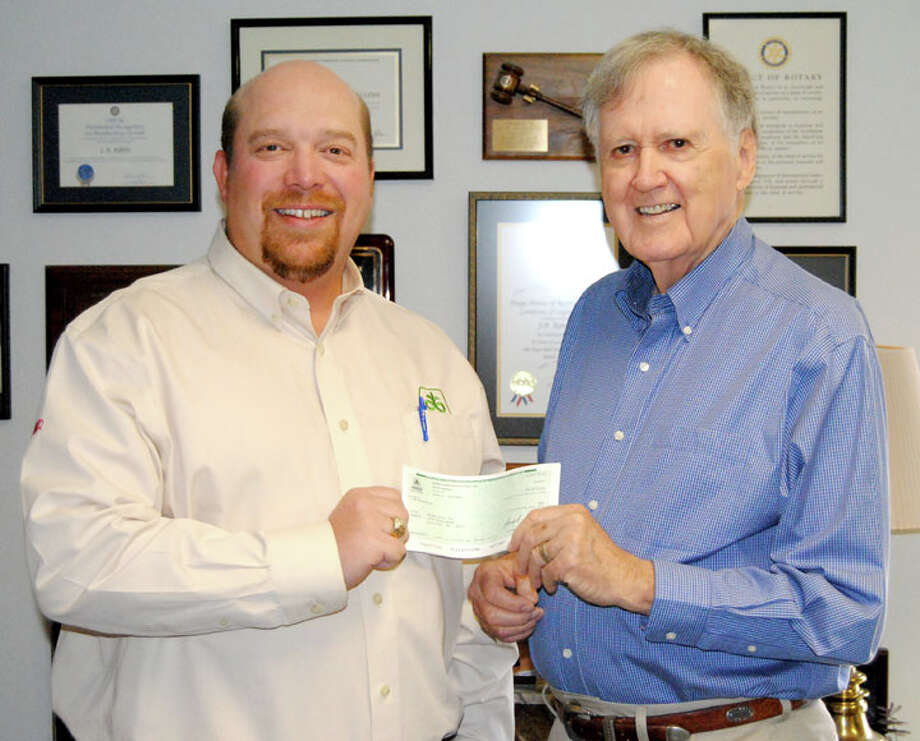 Jeff Miller (left), an account manager for DuPont Pioneer in Plain view, presents J.B. Roberts, board chairman of Hunger Plus, Inc., with a $1,000 grant for use locally. The funds will be used to assist such local agencies as the Faith In Sharing House (FISH) and The Salvation Army. Photo: Doug McDonough/Plainview Herald