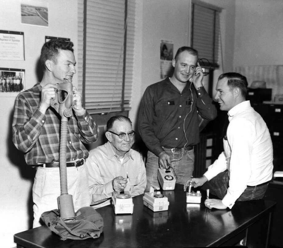Herald File PhotoIn 1962 the Soil Conservation Service staff was equipped to check for radioactive fallout. Jesse Jackson (left) is shown holding an oxygen mask; Earl Raper and Silas Flournoy examine radiological survey equipment; and Joe Blevins holds dose pencils used to determine radiation exposure levels.