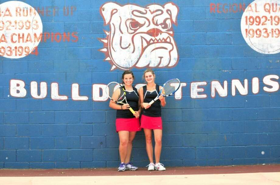 HS girls doubles duo of sophomore M'Kinna Decker (left) and teammate Elizabeth Earhart were the only two Bulldog netters to make it to the second day of the recent District 3-4A tournament. Best friends on and off the court, the girls say their different personality traits help to balance each other out. Photo: Summer Morgan/Plainview Herald