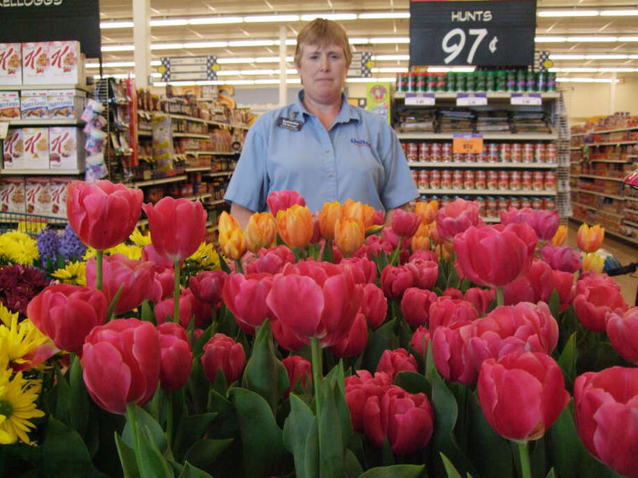 Symantha Pinkerton, non-food manager at United Supermarket, stands Friday in front of her store's supply of Mother's Day tulips. The grocery store sees mostly last-minute buyers on Mother's Day. Photo: Shanna Sissom Iverson/Plainview Herald
