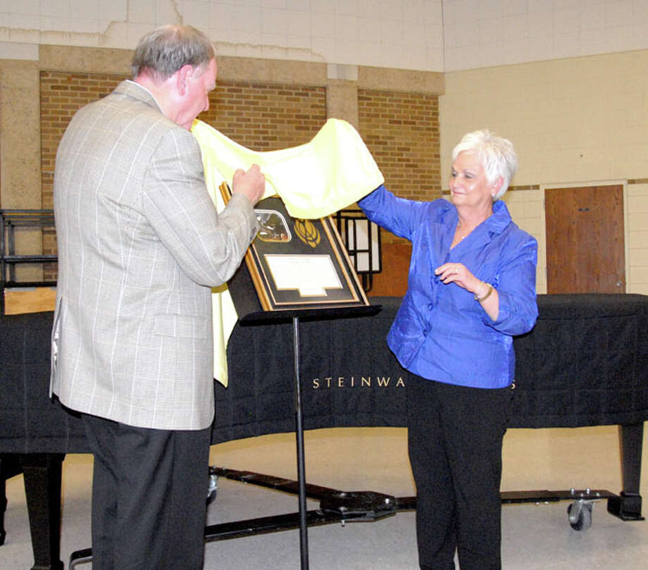 Wayland Baptist University PhotoJoe and Terri Jesko unveil a commemorative plaque that will hang in the practice room in memory of Pat McDaniel. The Jeskos led a group that purchased an Essex model upright piano in memory of McDaniel. It is part of Wayland's All Steinway Initiative.