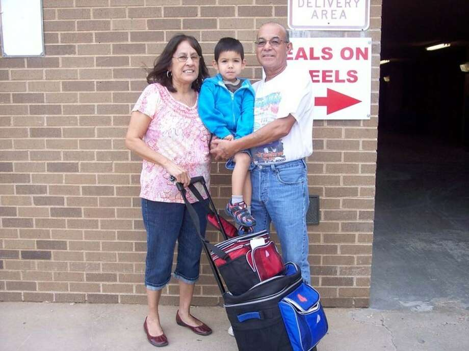 Courtesy PhotoJohn and Carolina Castro, shown with grandson, Noah Quijano, deliver a Meals on Wheels route every Thursday, and John serves as a MOW board member.