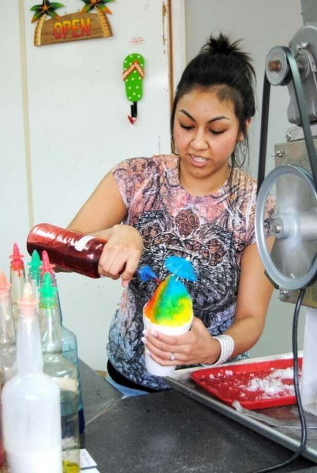 Doug McDonough/Plainview HeraldGabby Villarreal puts the finishing touches on a rainbow-hued snowcone Thursday at Frost Bites, 1004 N. Quincy. Villarreal says the snowcone stand, now in its 20th year, has been busy, particularly on hot afternoons like Thursday when the temperature reached into the mid-80s. Today shouldn't be quite as warm with a forecast high in the lower 70s. Saturday's high should reach into the mid-70s with Sunday warming into the lower 80s. There's a 20 percent chance of showers this morning.